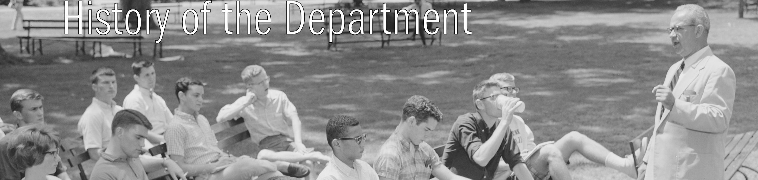 Caption - History of the Department. Black and white image of Bill Greer teaching class.